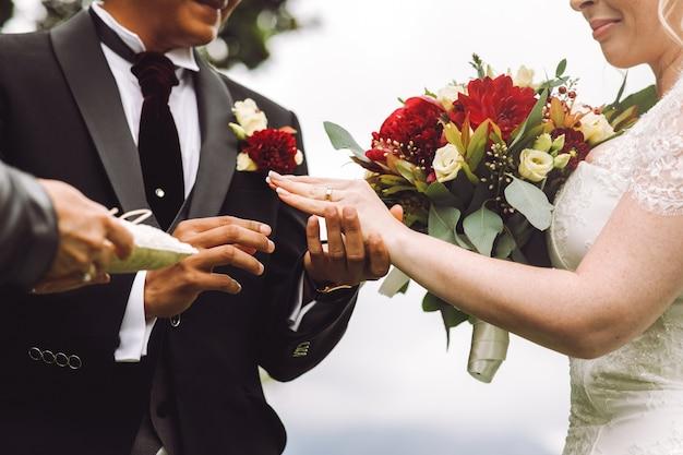 Noiva coloca aliança no dedo do noivo Foto gratuita