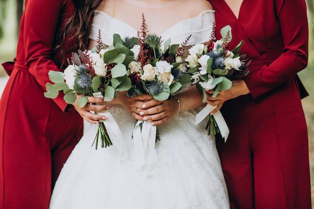 Noiva com buquê de casamento no meio de damas de honra Foto gratuita