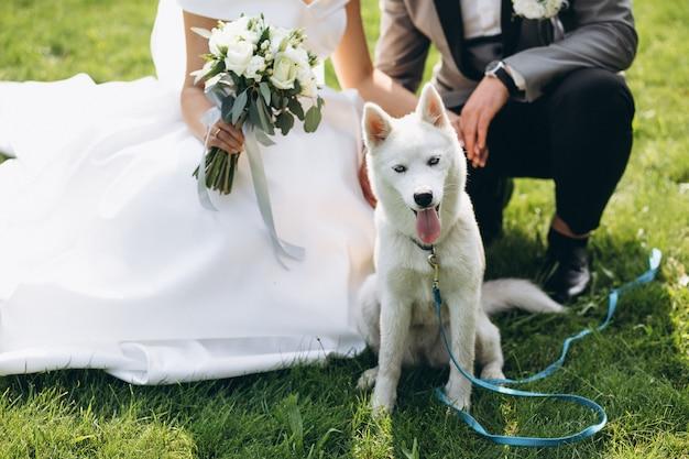 Noiva com o noivo com seu cachorro no dia do casamento Foto gratuita