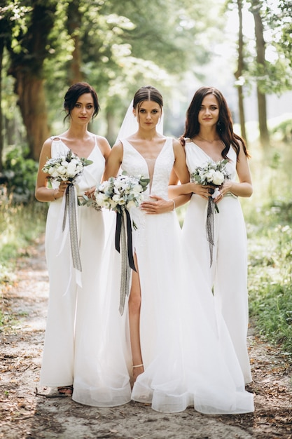 Noiva com suas damas de honra na floresta Foto gratuita