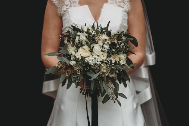 Noiva com um vestido de noiva branco segurando um lindo buquê de flores em preto Foto gratuita