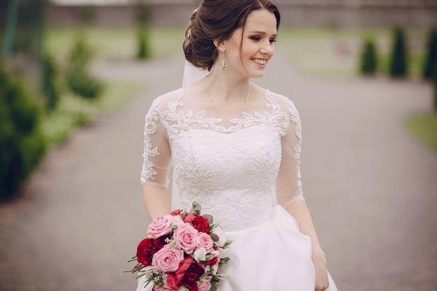 Noiva de sorriso com seu buquê Foto gratuita