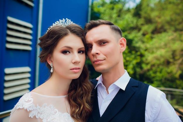 Noiva e noivo andando na cidade, dia do casamento, conceito de casamento. noiva e noivo em meio urbano. jovem casal subindo uma escada no dia do casamento. Foto Premium