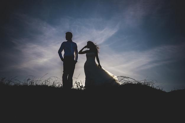 Noiva e noivo backlit em um por do sol na praia. Foto Premium