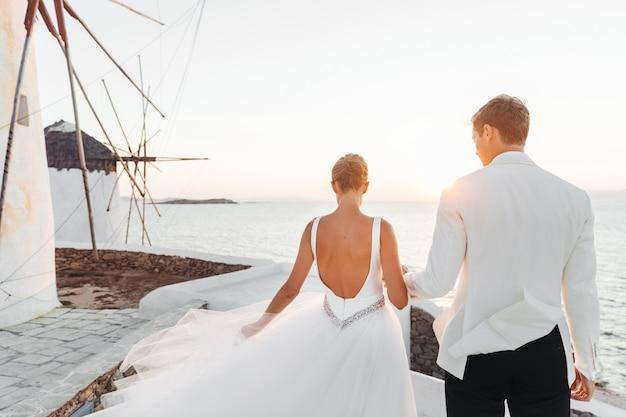 Noiva e noivo caminham em direção ao pôr do sol sobre o mar Foto gratuita
