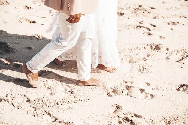 Noiva e noivo caminhando juntos ao longo da praia. casal de casamento romântico Foto gratuita