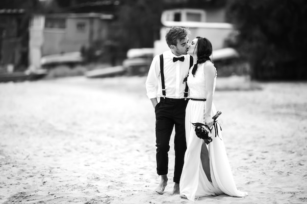 Noiva e noivo caminhando na praia, perto do mar e beijo. um lindo casal. Foto Premium