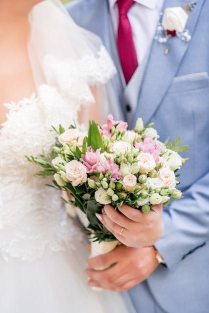 Noiva e noivo com buquê de casamento Foto Premium