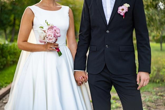 Noiva e noivo com um buquê. a noiva em um vestido branco peludo, o noivo em um terno de smoking azul. Foto Premium