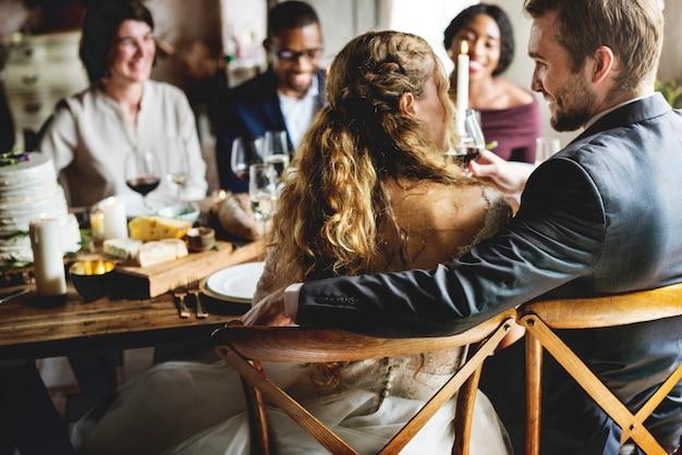 Noiva e noivo comendo com amigos na recepção do casamento Foto Premium