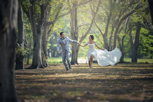 Noiva e noivo correndo e estacionar e de mãos dadas Foto Premium