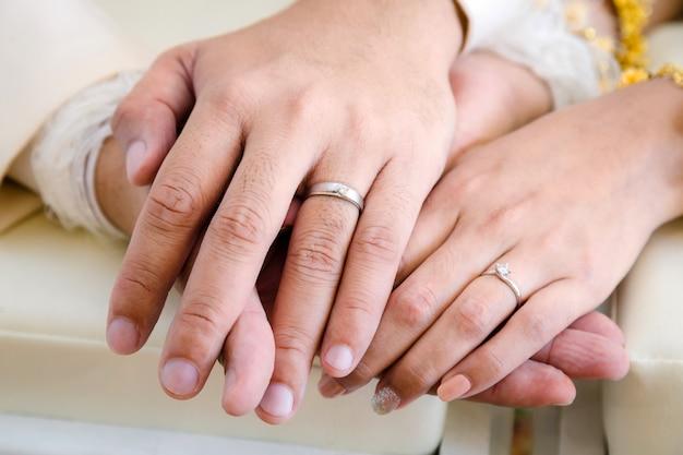 Noiva e noivo de mãos no dia do casamento Foto Premium