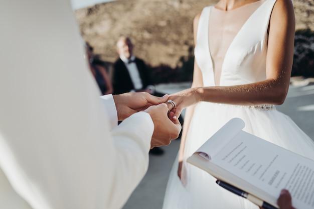 Noiva e noivo em roupas de verão leve as mãos uns aos outros durante a cerimônia Foto gratuita