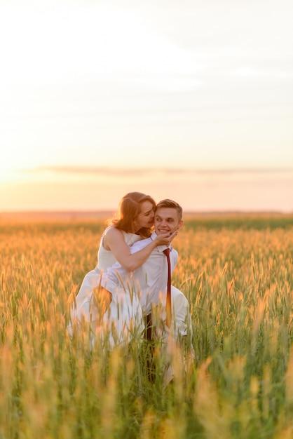 Noiva e noivo em um campo de trigo. um homem carrega um ente querido nas costas. Foto Premium