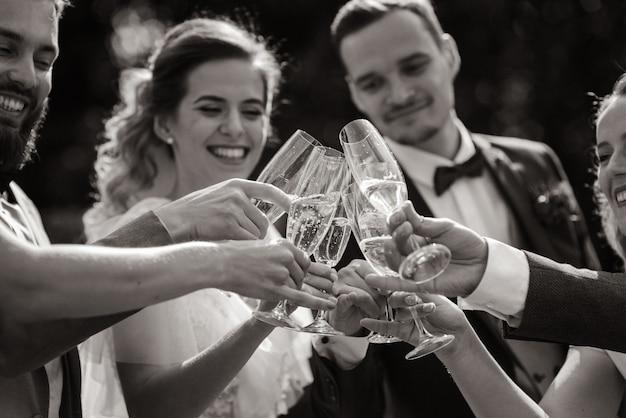 Noiva e noivo estão bebendo champanhe com os melhores amigos ao ar livre com sorrisos sinceros, vista monocromática Foto gratuita