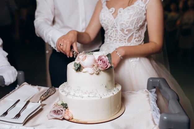 Noiva e noivo estão cortando decorado com flores, bolo de casamento Foto gratuita