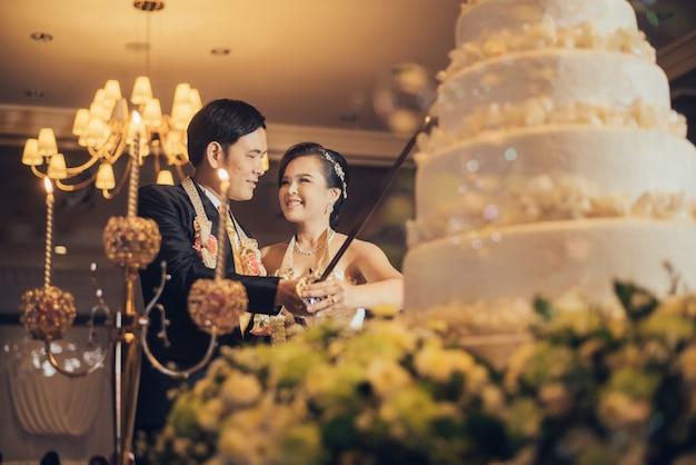 Noiva e noivo estão cortando o bolo para a celebração no dia do casamento Foto Premium