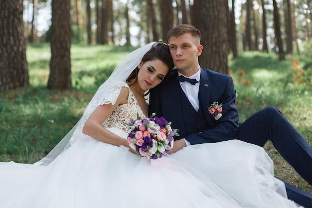 Noiva e noivo felizes após a cerimônia de casamento na natureza. sentimentos de ternura por noivos no parque verde. dia do casamento. Foto Premium