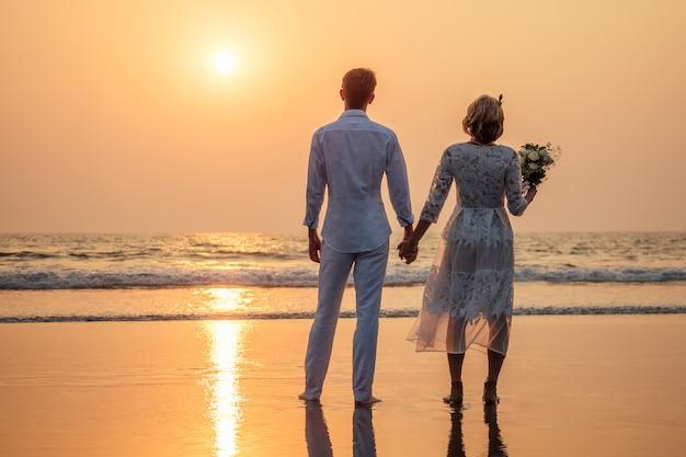 Noiva e noivo felizes na praia Foto Premium