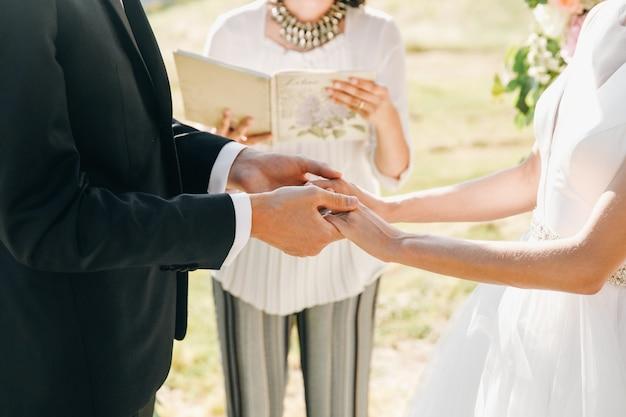 Noiva e noivo mantêm as mãos juntas durante a cerimônia Foto gratuita