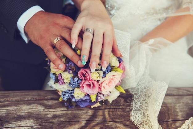 Noiva e noivo mãos com anéis de casamento Foto Premium