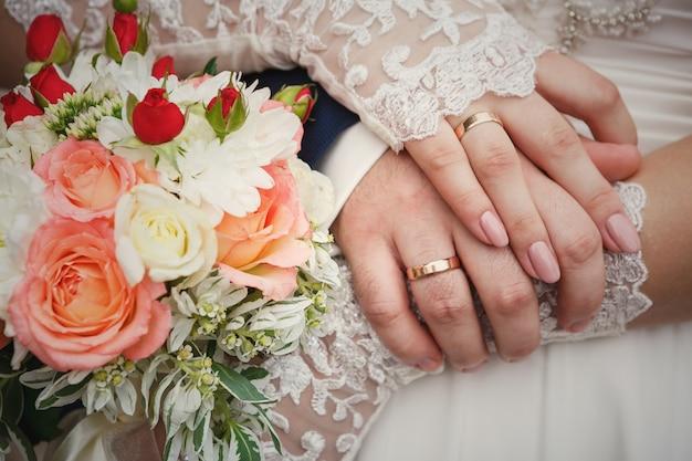 Noiva e noivo mãos com buquê de casamento e anéis Foto Premium