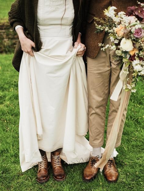 Noiva e noivo mostram seus sapatos no fundo de um campo, gramado verde Foto Premium