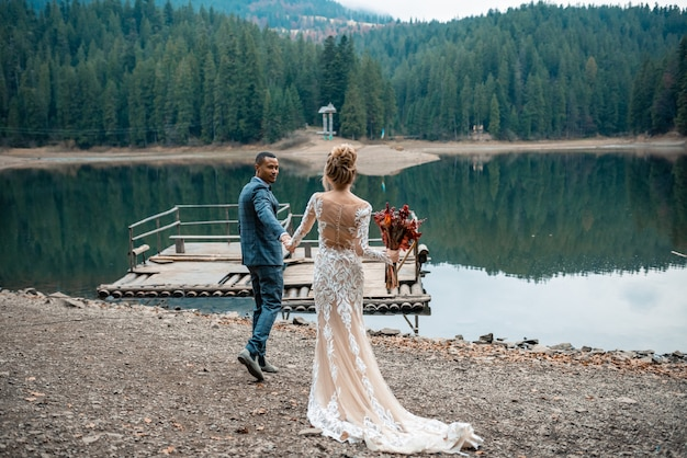 Noiva e noivo na cerimônia de casamento no lago bonito. Foto Premium