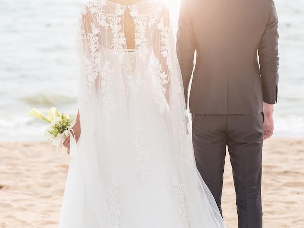 Noiva e noivo na praia com um momento romântico Foto Premium