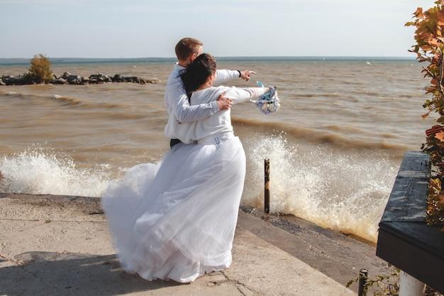 Noiva e noivo na praia olhando para o mar. Foto Premium