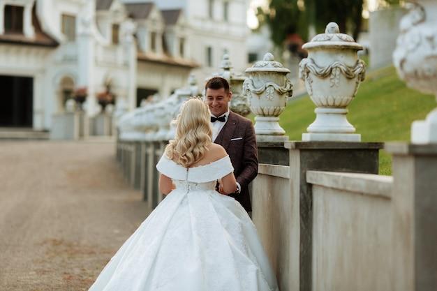 Noiva e noivo no casamento dia caminhando ao ar livre na natureza da primavera. casal nupcial, mulher feliz recém-casado e homem abraçando no parque verde. casal apaixonado casamento ao ar livre. Foto Premium