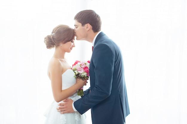 Noiva e noivo no quarto muito brilhante em casa Foto Premium