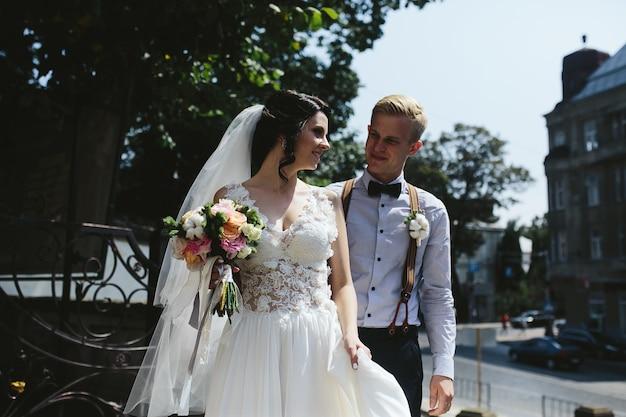 Noiva e noivo posando nas ruas da cidade velha Foto gratuita