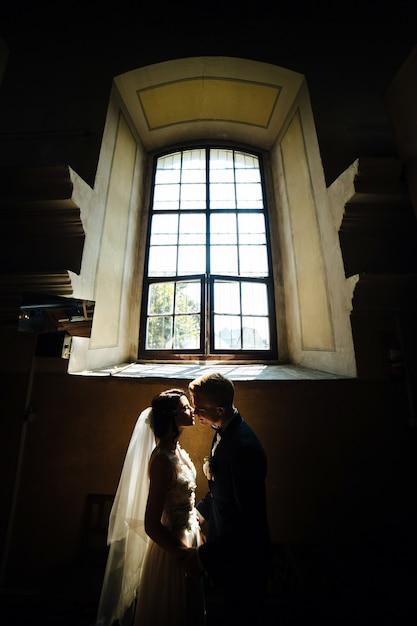 Noiva e noivo posando no fundo de uma grande janela Foto gratuita