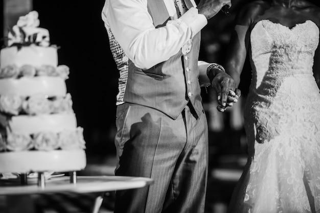 Noiva e noivo pronto para cortar o bolo de casamento branco clássico Foto gratuita