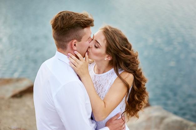 Noiva e noivo sentado na praia e beijando Foto Premium