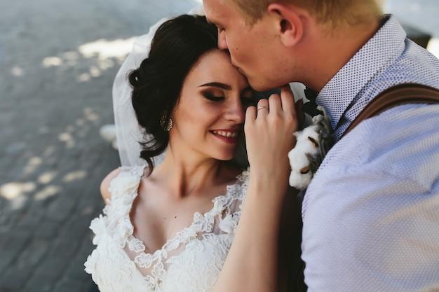 Noiva e noivo sentados no banco e se divertindo Foto gratuita