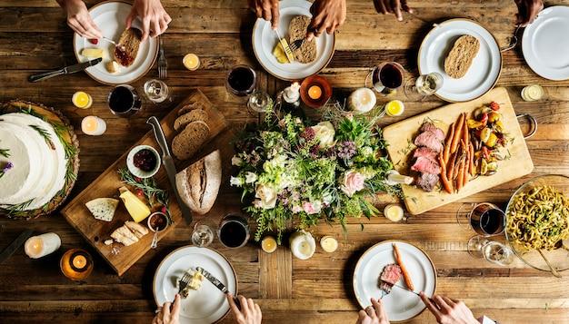 Noiva e noivo tendo refeição com amigos na recepção do casamento Foto Premium