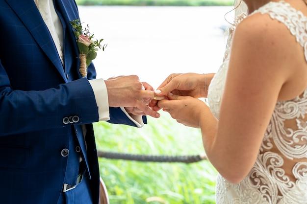 Noiva e noivo trocando alianças durante o dia Foto gratuita