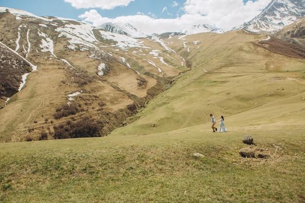 Noiva e o noivo estão andando na grama no verão em altas montanhas Foto gratuita