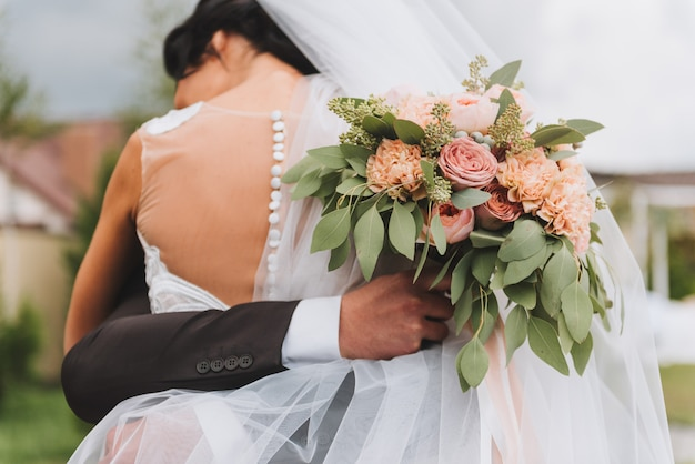 Noiva, em, abra aberto, vestido, abraçar, dela, noivo, quem, é, segurando, um, buquê casamento, ao ar livre Foto Premium