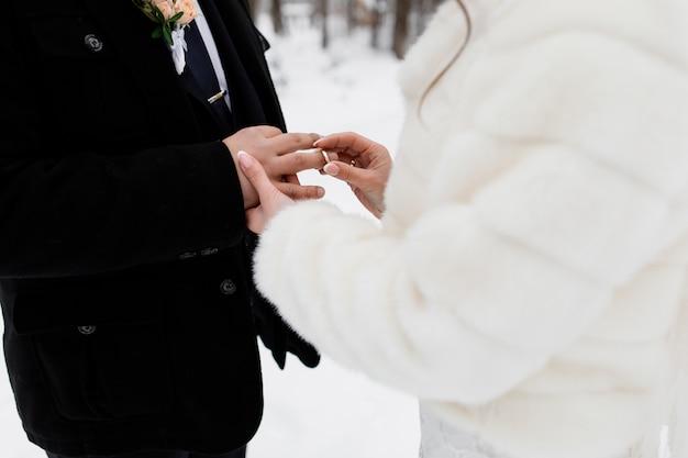 Noiva está colocando um anel no dedo do noivo ao ar livre Foto gratuita