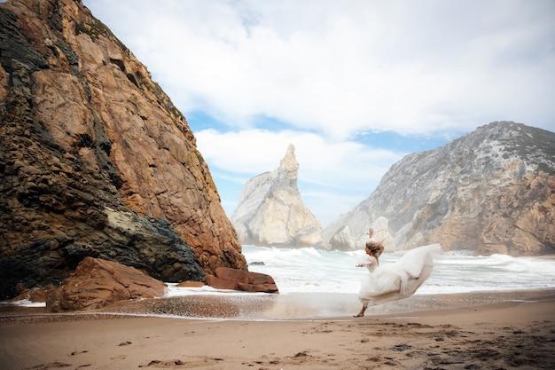 Noiva está correndo na areia entre as pedras na praia Foto gratuita