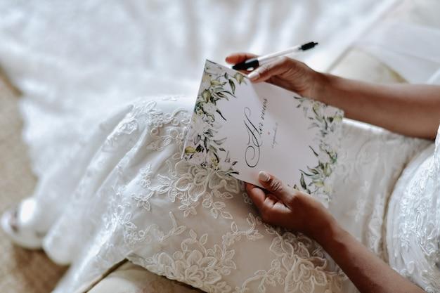Noiva está escrevendo os votos de casamento, símbolos do dia do casamento Foto gratuita
