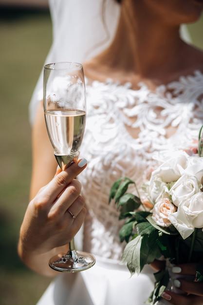 Noiva está segurando uma taça de champanhe e um buquê de casamento ao ar livre Foto gratuita