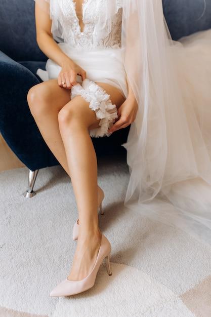 Noiva está vestindo uma liga de casamento na perna, sentado na poltrona Foto gratuita