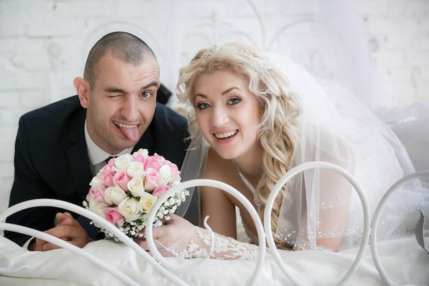 Noiva feliz com um buquê de rosas e o noivo alegre que está colocando a língua para fora, deite-se em uma cama no quarto Foto Premium