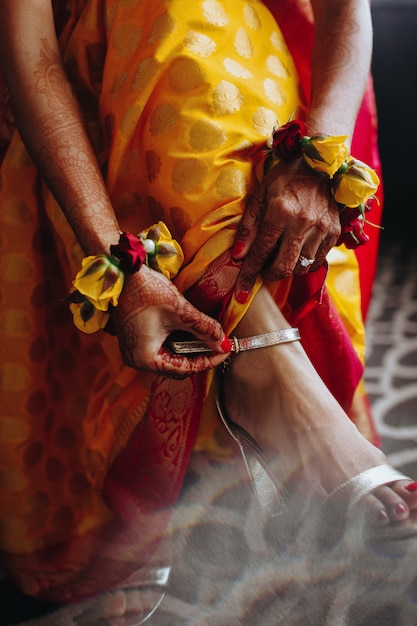 Noiva hindu coloca pulseira tradicional na perna Foto gratuita