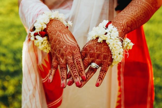 Noiva hindu mostra as mãos cobertas de tatuagens de hena Foto gratuita