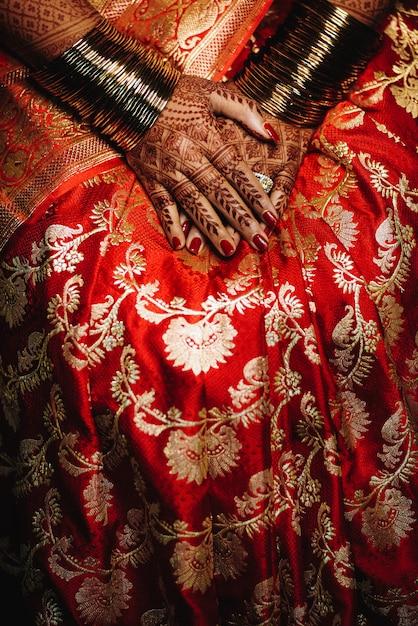 Noiva hindu mostra seus anéis de casamento nas mãos com henna tatt Foto gratuita
